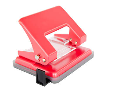 punch press: Red office paper hole puncher on white background