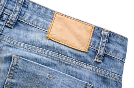 inner wear: Blank leather jeans label sewed on a blue jeans. on white background.