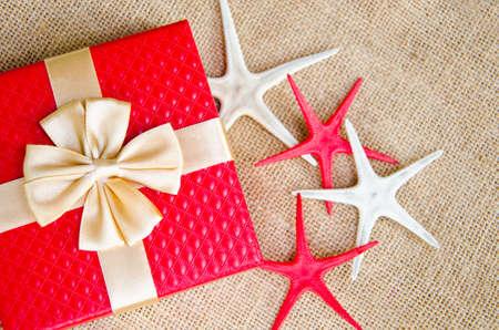 fish star: caja de regalo rojo con cinta de oro y estrellas de mar sobre fondo saco