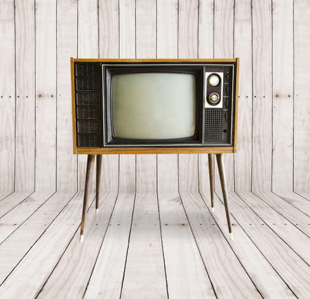 retro tv: old vintage television on wood background.