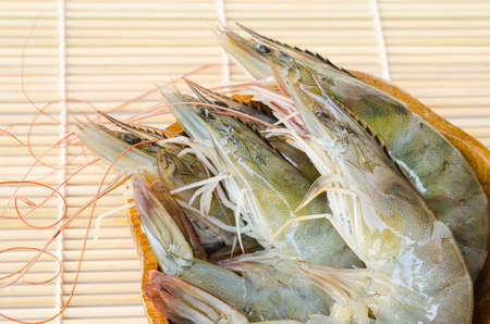 in a raw: raw shrimps in cup on wooden mat.