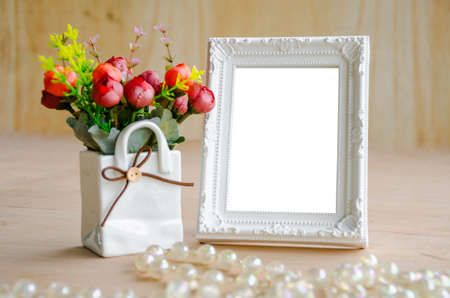Flowers vase and blank white picture frame on wooden background Stock Photo