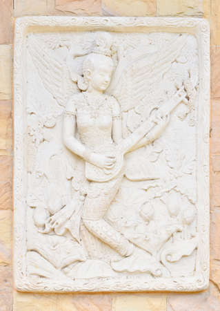 garden statuary: Statue of a woman playing fiddle . Thai ancient stone carving Stock Photo