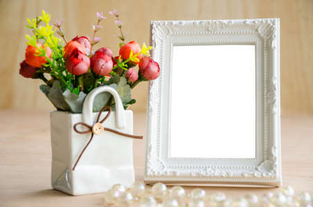 Flowers vase and vintage white picture frame on wooden desktop, clipping path