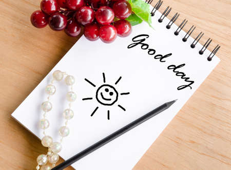life is good: Good day wording on white diary and red grape on wooden background.
