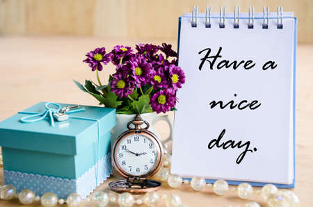 open diary: Have a nice day. Open diary, pocket watch, gift box and flower on wooden backgroudn. Stock Photo