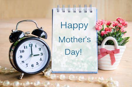 agradecimiento: Las madres tarjeta del día y despertador con flores sobre fondo de madera. Foto de archivo
