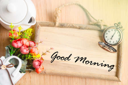 Good morning text in blank wooden photo frame with flower on wooden background.