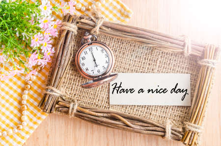 good time: Have a nice day card and pocket watch at 6 AM with flower on wooden background. Stock Photo