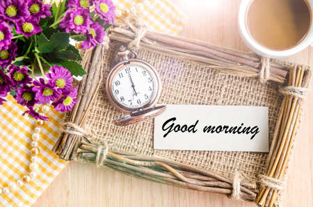 morning breakfast: Good morning word on tag paper, pocket watch, violet flower and coffee in cup on wooden background.