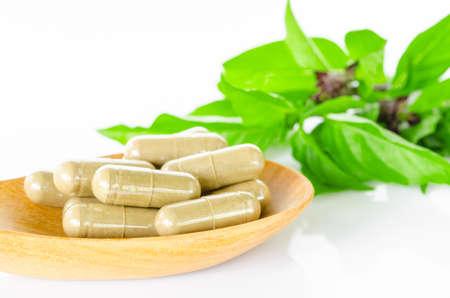pastillas: Amarillo drogas medicina c�psula de hierbas en cuchara de madera y hojas verdes sobre fondo blanco.