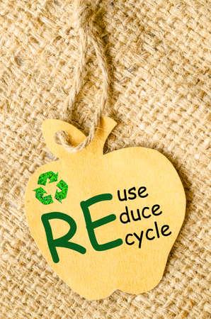 reduce reutiliza recicla: Recicle signo y Reducir, Reutilizar, Reciclar redacci�n de reciclaje de papel etiqueta de forma de la manzana en el fondo saco. Recicle el concepto de papel.