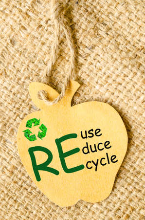 apple sack: Recycle sign and Reduce, Reuse, Recycle wording on paper recycle apple shape tag on sack background. Recycle paper concept. Stock Photo