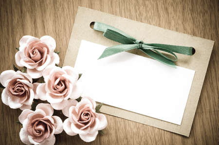 Vintage greeting card and rose flower on wooden background.