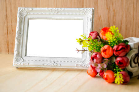frame photo: Flowers vase and vintage white picture frame on wooden desktop, clipping path