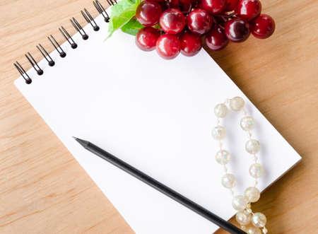 buena salud: Diario en blanco Abrir y uva roja sobre fondo de madera.