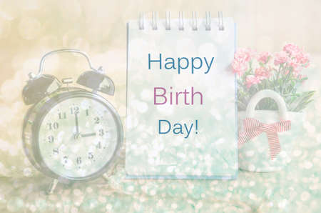 birth day: Happy birth day diary and alarm clock with flowers. Soft light background. Stock Photo