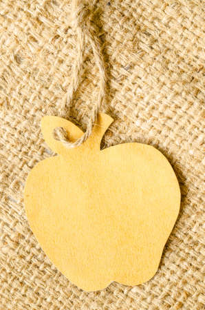 apple sack: Brown blank tag apple shape on sack background. Recycle paper concept.