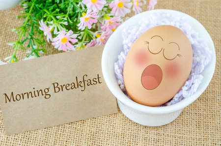 jowl: Morning breakfast tag. Eggs sleep with Expression Face in white cup and flower on sack background.