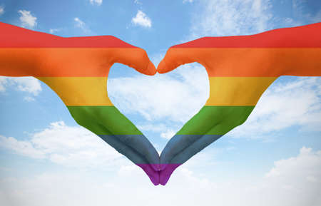 Hands painted as the rainbow flag forming a heart, symbolizing gay love on blue sky. Fredom concept.