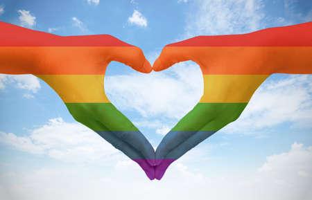 lesbianas: Manos pintadas como la bandera del arco iris que forman un corazón, símbolo de amor gay en el cielo azul. Concepto fredom.