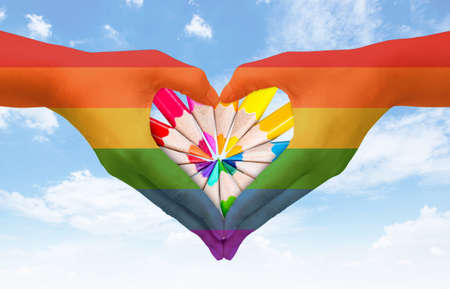 transgender gay: Hands painted as the rainbow flag forming a heart, symbolizing gay love on blue sky. Fredom concept.