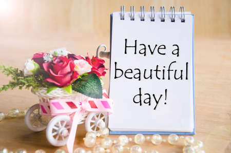 nice: Have a nice day on open diary and and red rose basket on wooden background.