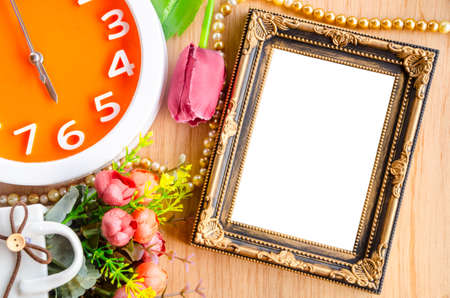 GLOD: Flowers vase and vintage white picture frame on wooden desktop, clipping path