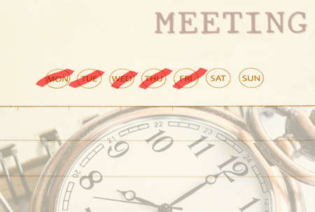 up to date: Close up meeting date on diary with pocket watch.