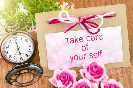 木製の背景のピンクのローズとタグとポケットの時計で自分の世話をします。