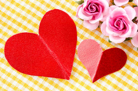 noteboard: Red heart tag paper and pink rose flower on beautiful fabric background.