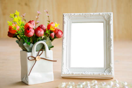 blank photo: Blank vintage photo fame and flower on wooden background. Save with clipping path.