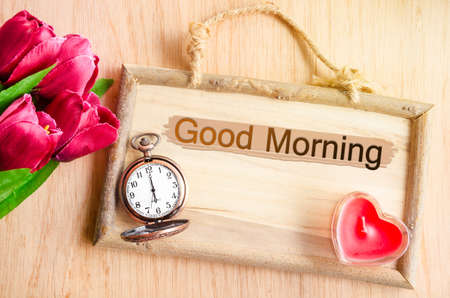 red morning: Good morning. Clock and red tulip with red candle heart shape on wooden background. Stock Photo