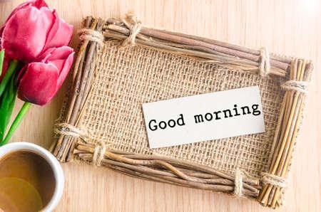 comida rica: Buenos días etiqueta de papel en el marco de fotos saco y de café con el tulipán rojo sobre fondo de madera.