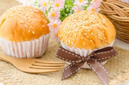 white sesame seeds: Bread bun with white sesame seeds and wooden spoon on white background