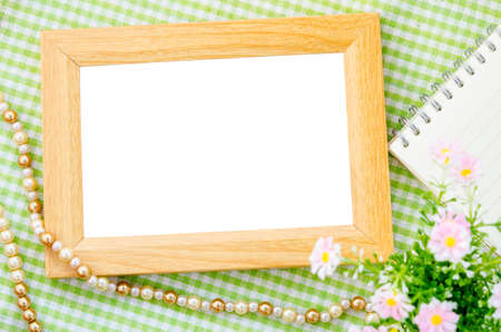 open diary: Blank vintage wooden photo frame and open diary with pink flower on fabric background