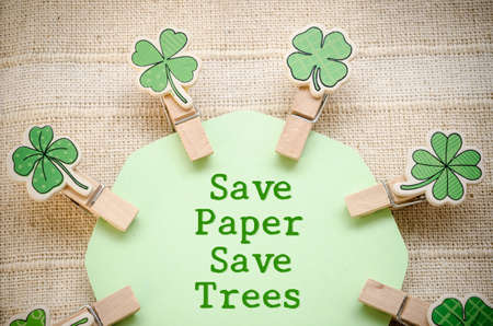 Save paper save trees on green paper and leaf wooden clamps on fabric background
