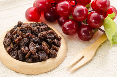 Raisins on a wooden dish and fresh red grapes on fabric background.