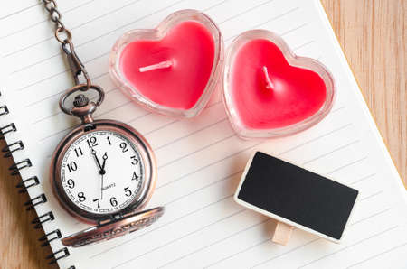 bougie coeur: Red heart candle and pocket watch with open diary on wooden background.