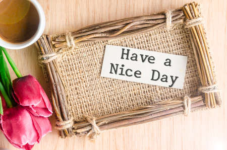 nice day: Have a nice day paper tag in sack photo frame and coffee with red tulip on wooden background. Stock Photo