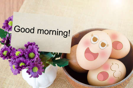 Good morning card and smile face eggs in wooden bowl on woden background. Zdjęcie Seryjne
