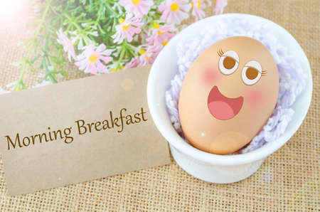 morning breakfast: Morning breakfast and smile face egg in white cup with flower on sack background. Stock Photo