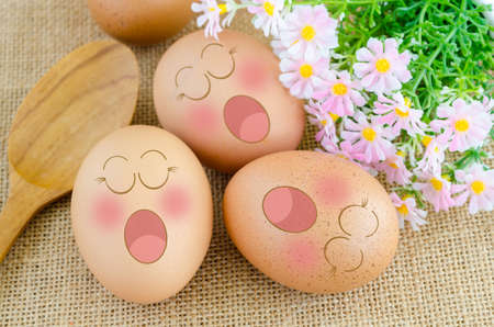 jowl: Eggs sleep in Expression Face ans wooden spoon with flower on sack background. Stock Photo