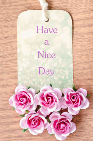 papier lettre: Have a nice day on beautiful tag pink rose on wooden background. Banque d'images