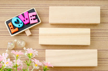 valentine heart: LOVE wording and blank wooden tag with flower on wooden background.