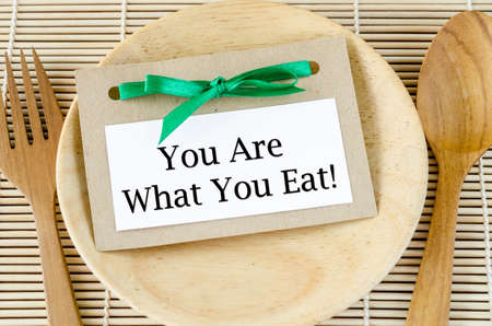 strong message: Healthy lifestyle concept - you are what to eat reminder words  in paper tag on dish and spoon wooden. Stock Photo
