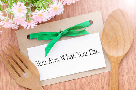 recommendations: You are what you eat message in paper tag with wooden spoon on wooden background. Healthy concept.