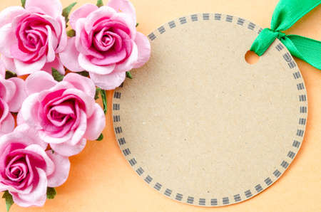 Blank brown paper tag and pink rose for your text on orange color background.