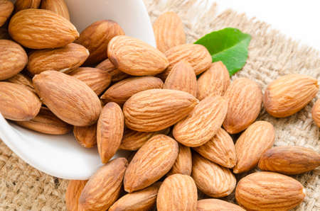 almond: Almonds in white bowl with green leaf on sack background. Stock Photo