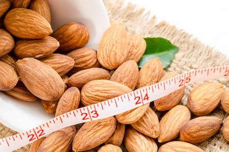 metro de medir: Almond y metro que mide con la hoja verde sobre fondo saco. Concepto de la dieta.